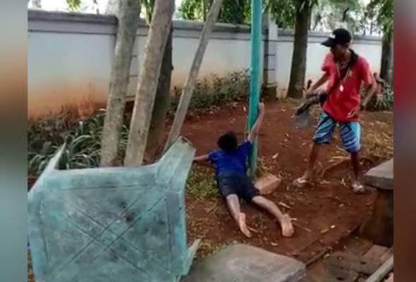 Video yang memaparkan kanak-kanak lelaki itu tertiarap dengan tangannya melekat pada tiang elektrik. -Video viral | Astro Awani