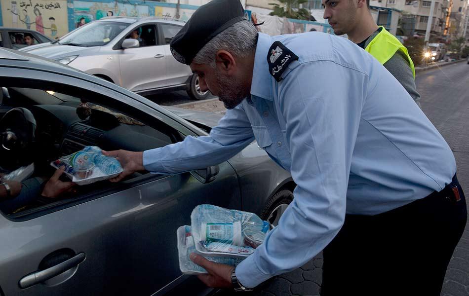 Seorang pegawai polis mengedarkan makanan ringan kepada pengguna jalan raya di Bandar Gaza sejurus sebelum waktu berbuka puasa pada 13 Mei 2019. - Foto AP/Hatem Moussa
