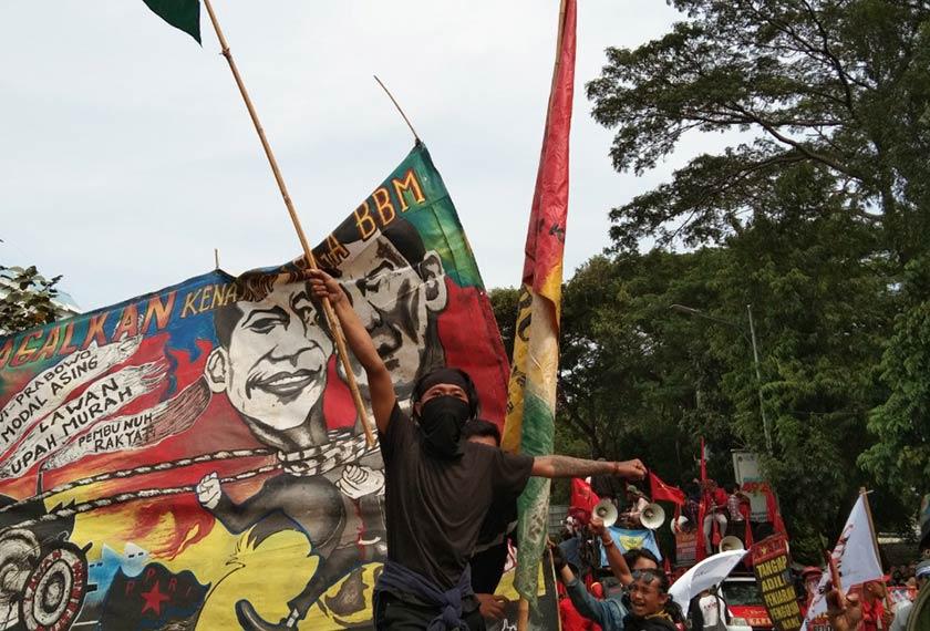 Seorang wakil kesatuan sekerja, Serikat Buruh Bumi Manusia (SEBUMI), melambaikan bendera organisasinya sebelum meneruskan perarakan ke Parlimen. Pasukan Ceritalah