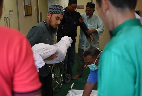 Bapa Nurul Amin Abdul Rahman, 36, (dua, kiri) dipapah ketika jenazah anaknya Mohammad Aimin, 7, diangkat untuk dibawa pulang di Unit Perubatan Forensik Hospital Temerloh pada Jumaat. - Foto BERNAMA | Astro Awani