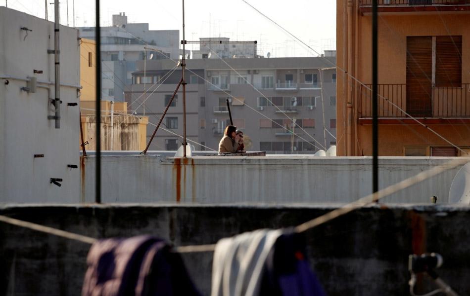 Sambutan Good Friday di Taranto, Itali ini hanya diraikan secara terasing, iaitu beberapa penduduk dilihat naik ke aras bumbung bangunan kediaman masing-masing untuk menikmati perayaan Easter. - Reuters/Alessandro Garofalo