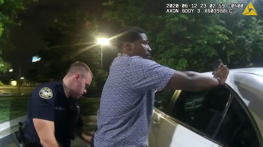 Former Atlanta Police Department officer Garrett Rolfe searches 27-year-old Rayshard Brooks in a Wendy's restaurant parking lot in a still image from the video body camera of officer Devin Bronsan in Atlanta, Georgia, U.S. June 12, 2020. Video taken June 12, 2020. Atlanta Police Department/Handout via REUTERS