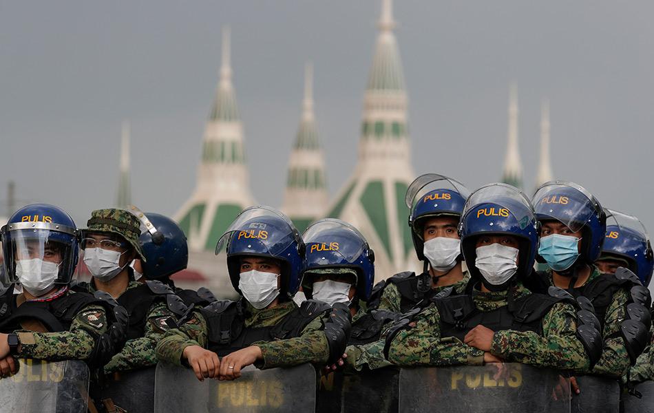 Anggota polis memakai pelitup muka ketika melakukan sekatan di hadapan laluan masuk ke Dewan Perwakilan di Metro Manila.
