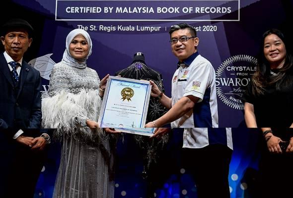 Haliza (dua, kiri) menerima sijil pengiktirafan dari MBOR daripada Ketua Pegawai Operasi MBOR Christopher Wong (dua, kanan) ketika majlis mempersembahkan tudung termahal di dunia bertatahkan kristal Swarovski hari ini. - Bernama | Astro Awani